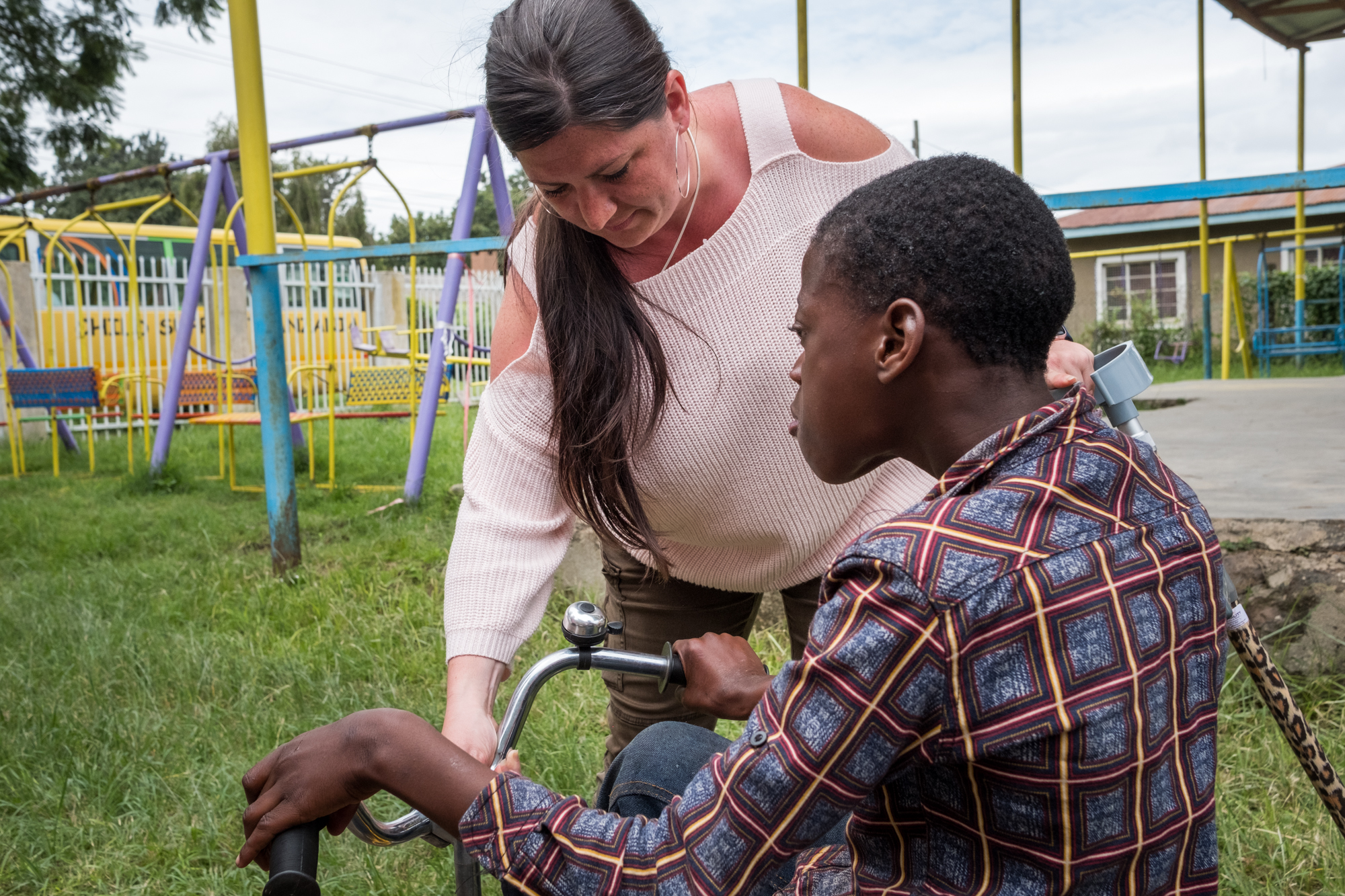 Holly helps a student (John Casto Mbawala) ride a bicycle at Child Support Tanzania, a non-governmental organization located in Mbeya, Tanzania, that educates disabled children.