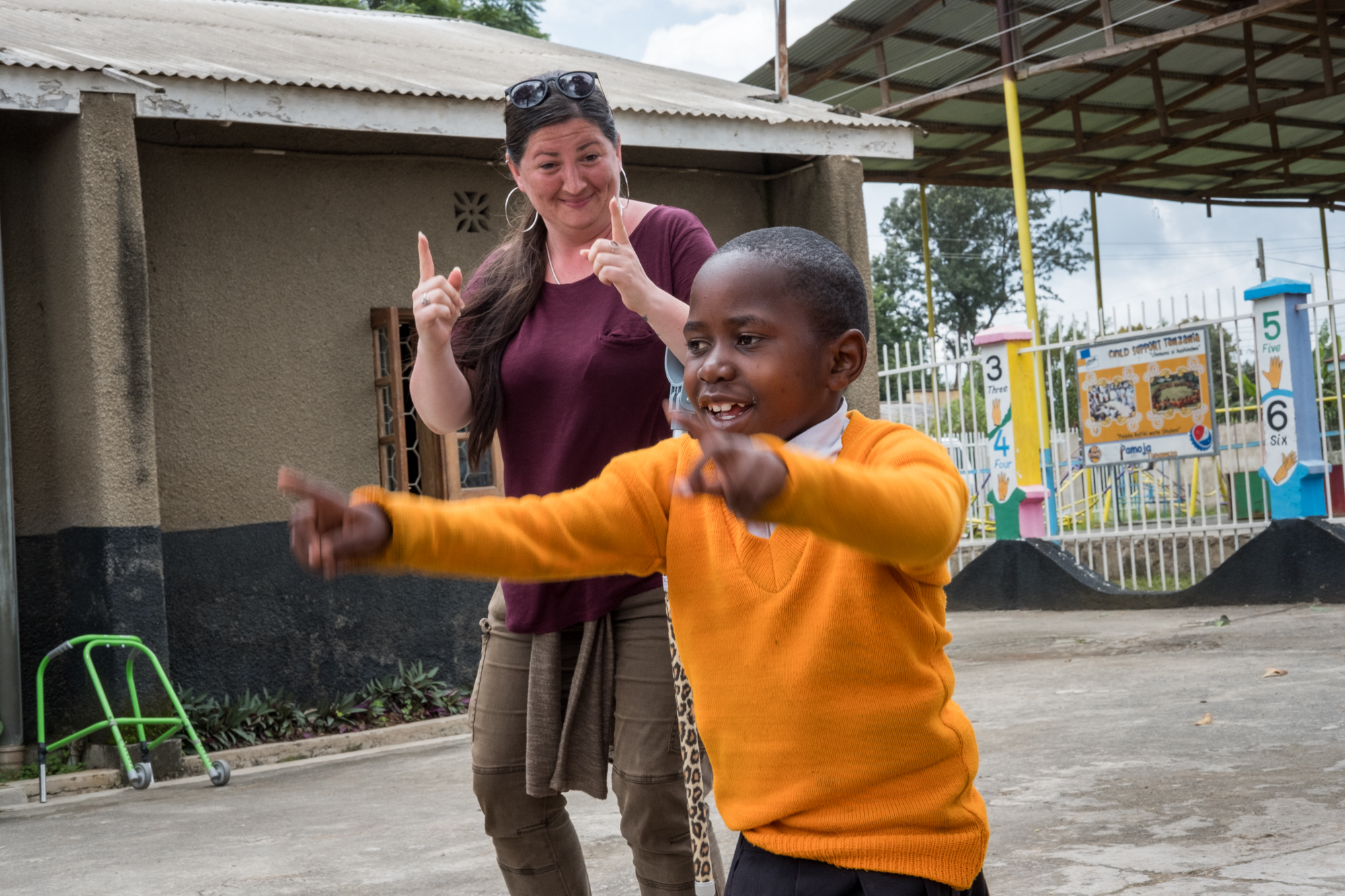 Holly dances alongside a student at Child Support Tanzania. Each day, students have the opportunity to play outside, socialize and listen to music.