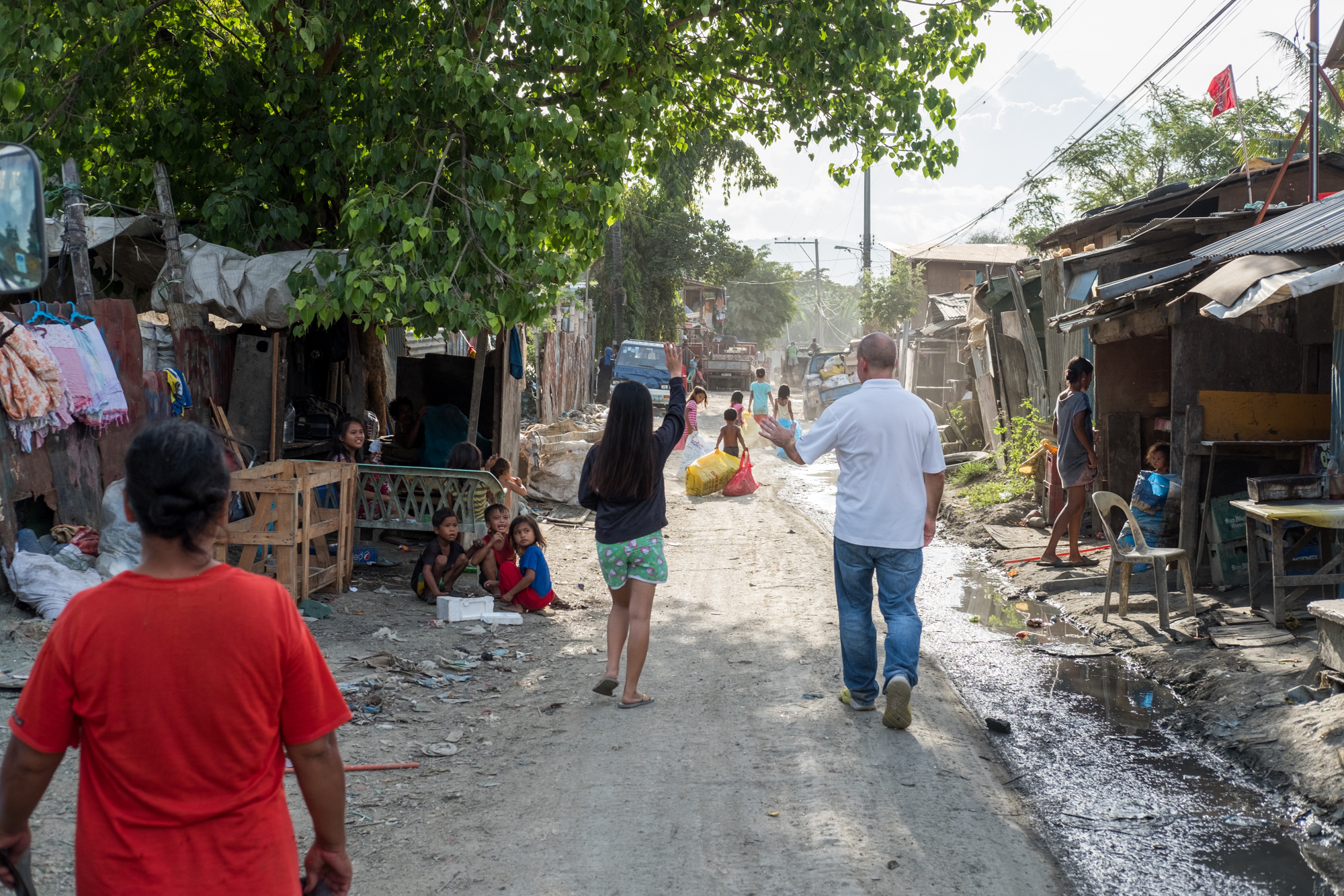 Frank Becker (right) walks with Marie Perly Anciano (left) on a road near the Mandaue Dump Site in Cebu, Philippines. Frank visits the dumpsites daily, and Marie is one of the many children that Frank has helped by donating school supplies and offering meals.