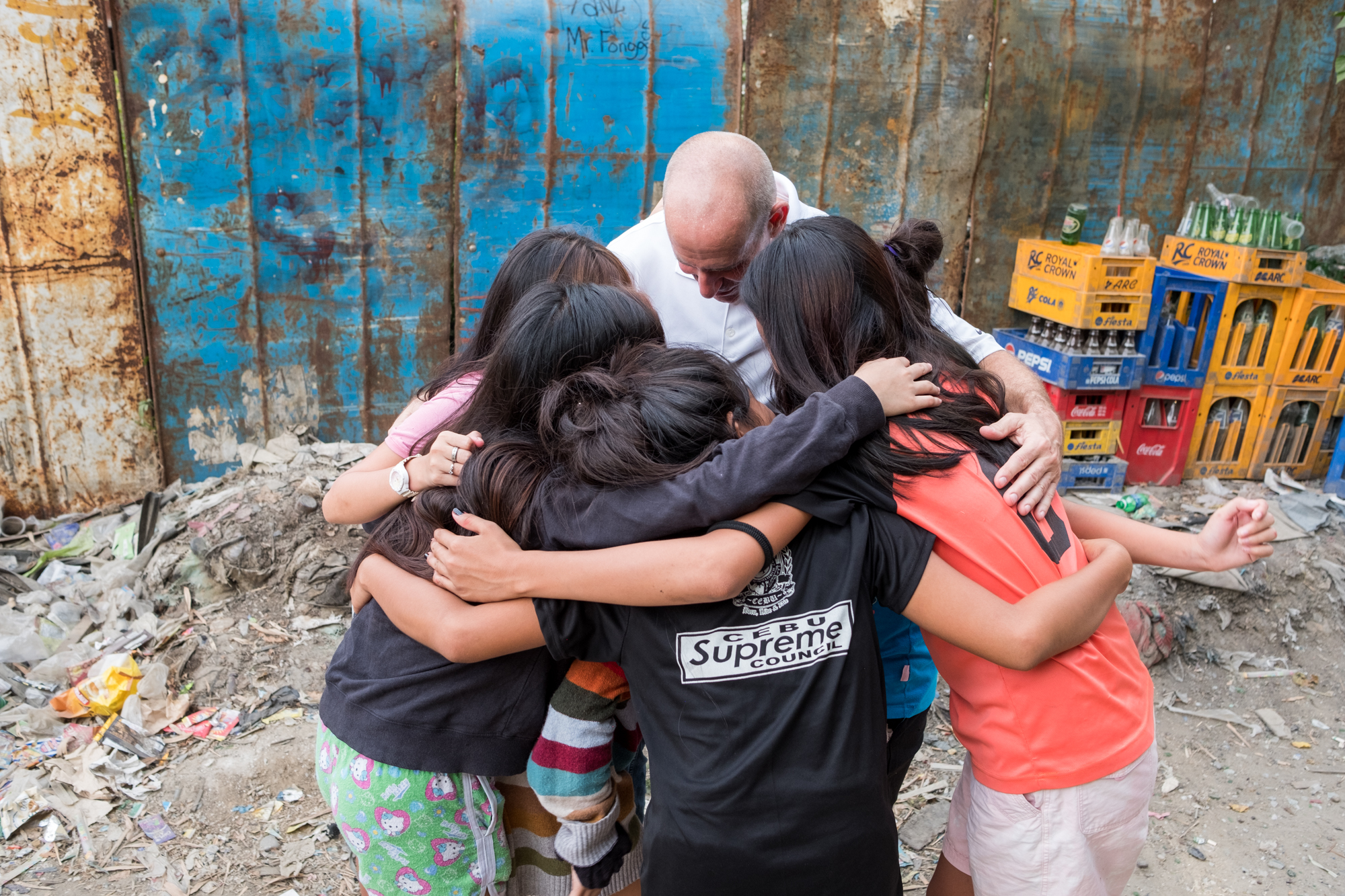 Frank Becker (center) has a group hug with several teenagers who live near the Mandaue Dump Site in Cebu, Philippines. Frank has been returning to this dumpsite for many years, so he has established strong bonds with teens and their families.