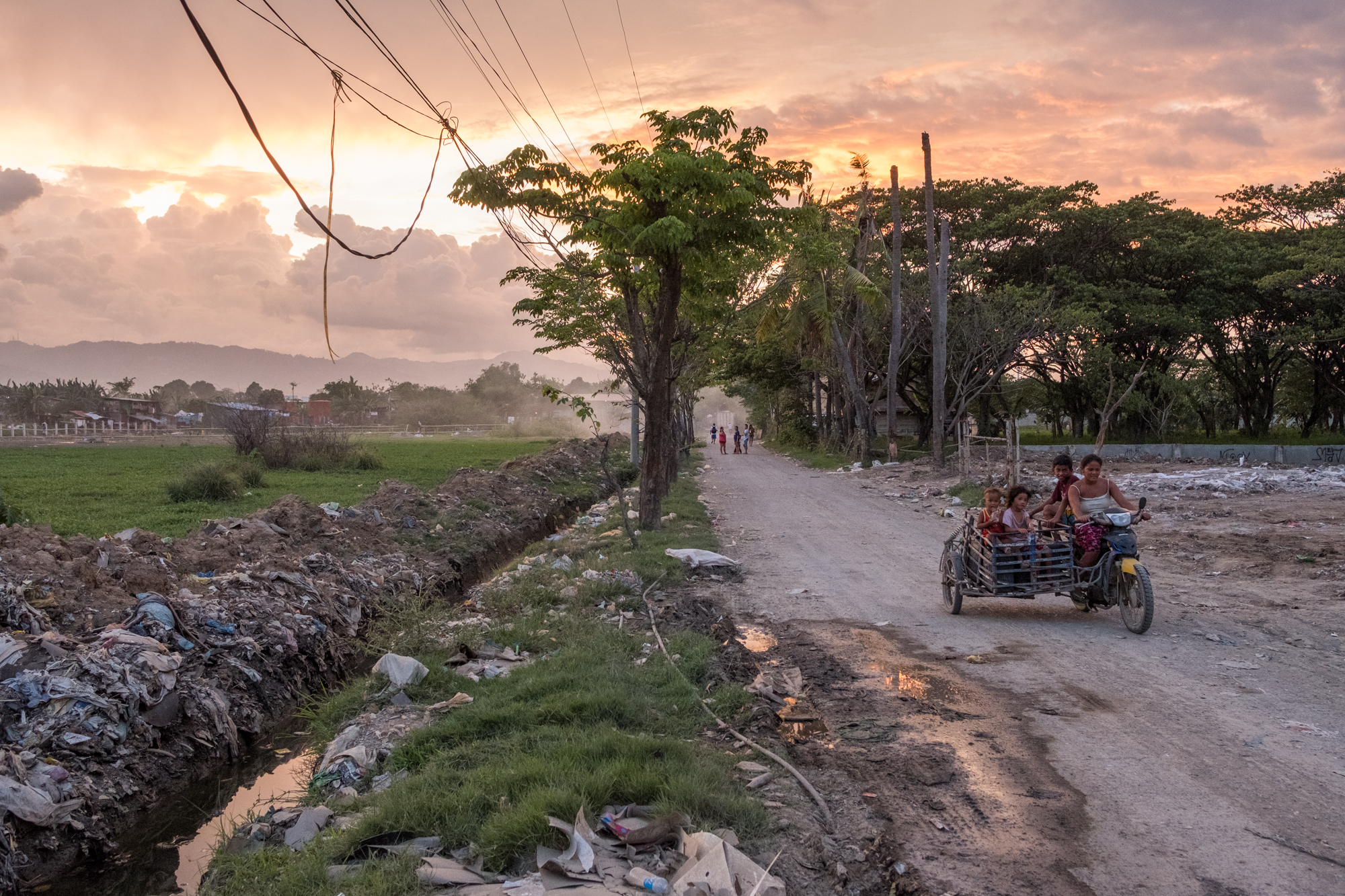 A colorful sunset illuminates the sky as people drive along a road near the Mandaue Dump Site in Cebu, Philippines.