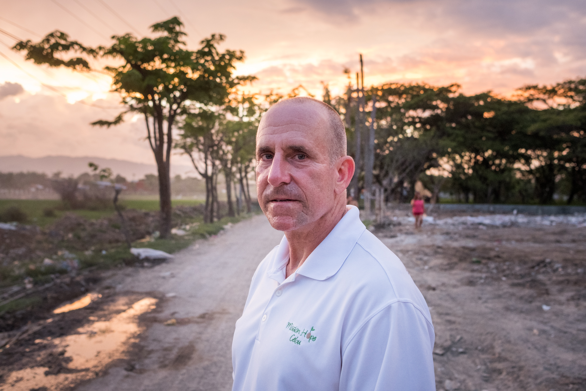 Frank Becker, a Hilton Team Member and Thrive Sabbatical winner, poses for a portrait on a road leading to the Mandaue Dump Site in Cebu, Philippines. Frank uses his personal vacation and savings to make a difference in this community.