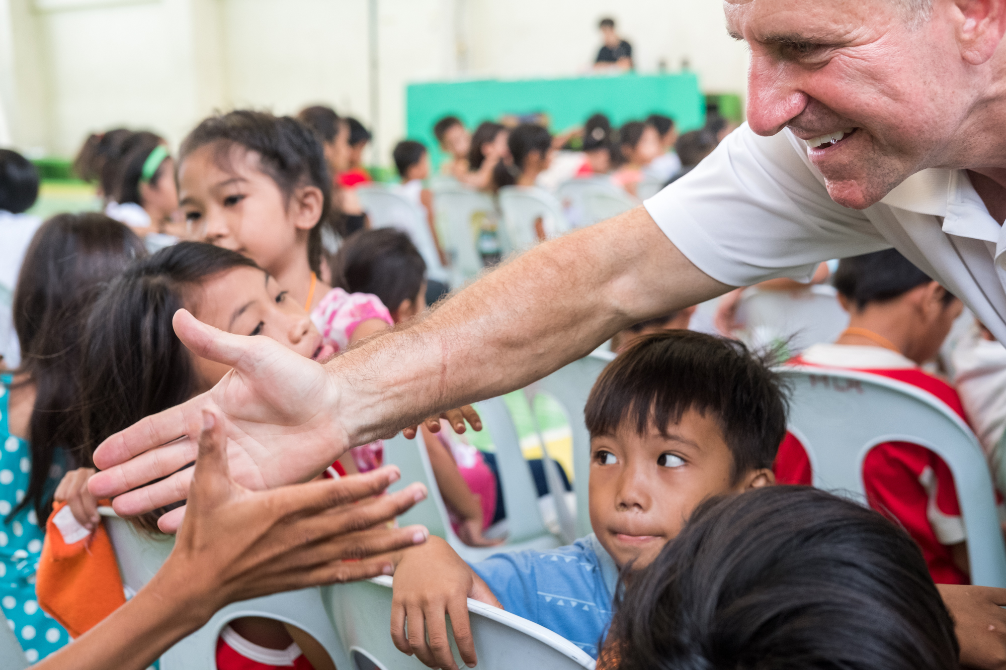 Frank Becker (right) greets children attending a community-giving event in Cebu, Philippines. During the event, Frank and local organizations include fun activities and games for the children.