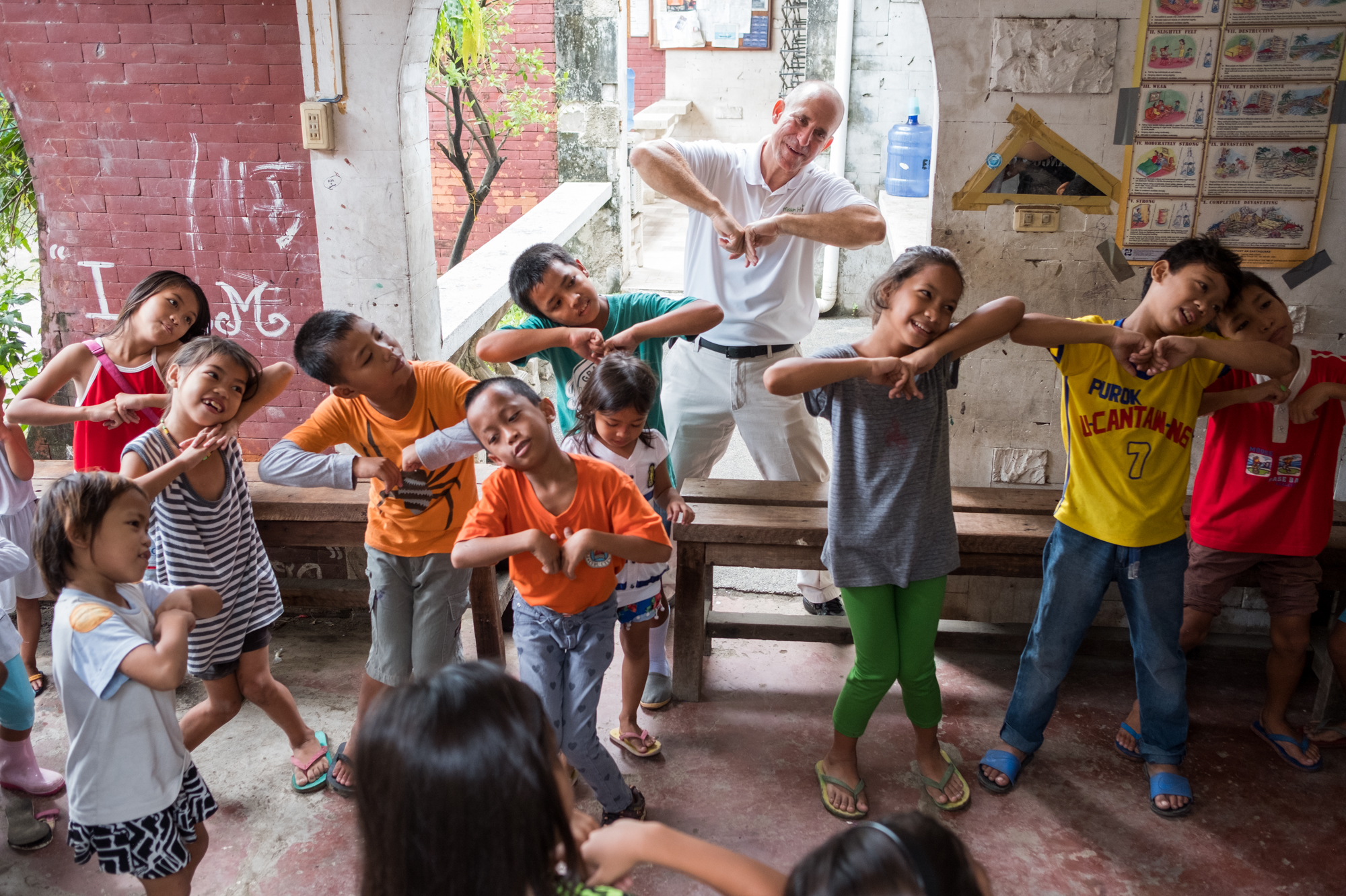 Frank Becker (back, center) dances with children during bible school at Living Bread Ministry in Cebu, Philippines. Frank instills faith-based exercises during the programs before offering school supplies and meals.