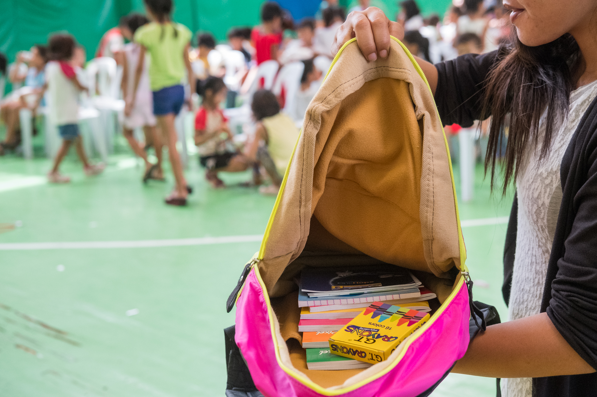 Rose Marie Plando (right) holds open a backpack filled with school supplies at a community-giving event in Cebu, Philippines. Frank works with organizations that donate the supplies. Sometimes he purchases the material himself.