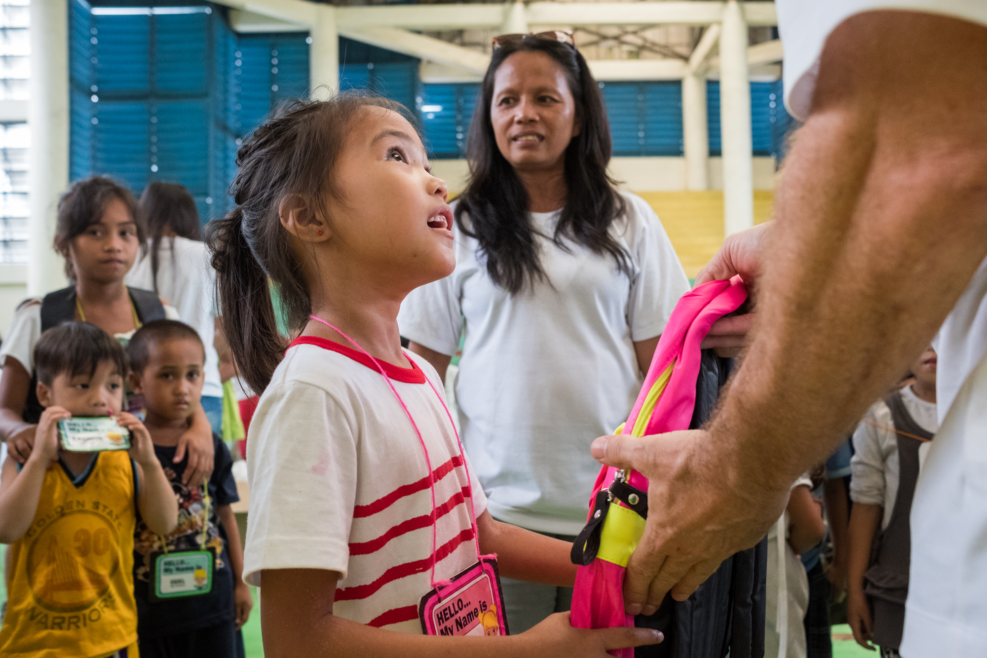 Frank Becker (off-camera right) distributes free backpacks filled with school supplies at a community-giving event in Cebu, Philippines.