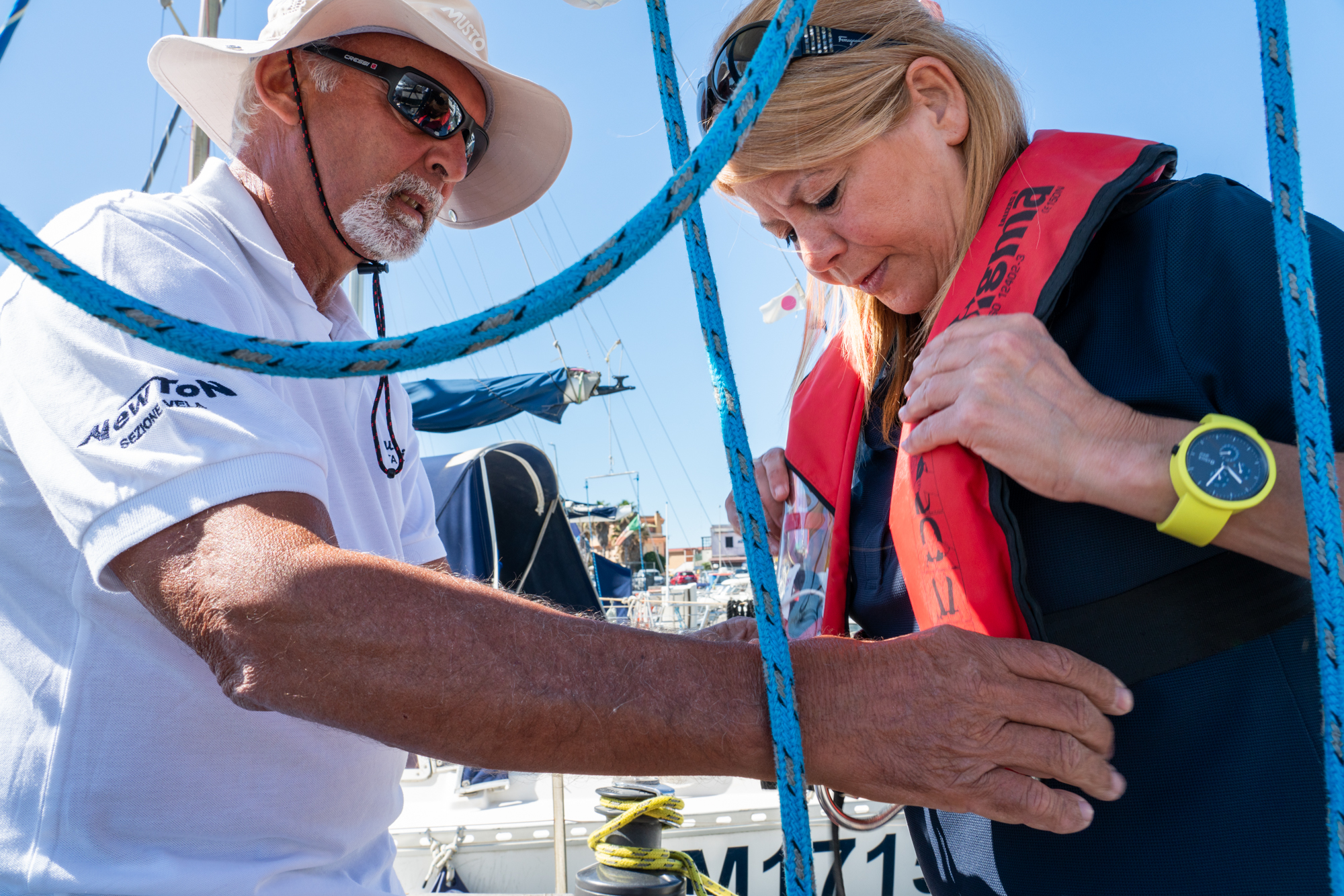 Patrizia (right) puts on a lifejacket with help from her sailing instructor, Claudio Rinaldini (left), at the Fiumicino Harbor in Italy.