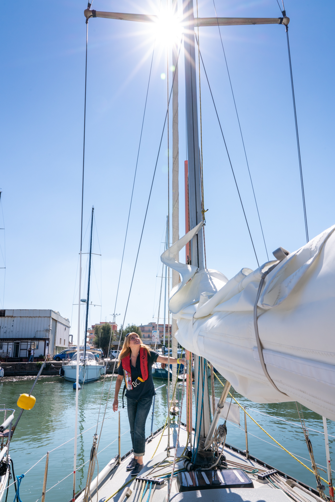 Patrizia performs routine checks of the sailboat before sailing off at the Fiumicino Harbor in Italy.