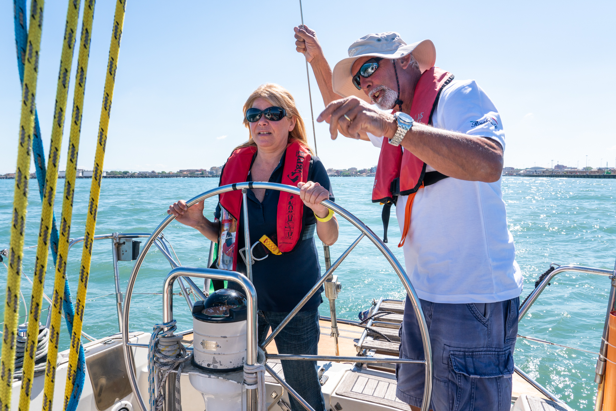 Patrizia Pilloni (left) steers the sailboat through Fiumicino Harbor in Italy as her instructor, Claudio Rinaldini, gives instruction.