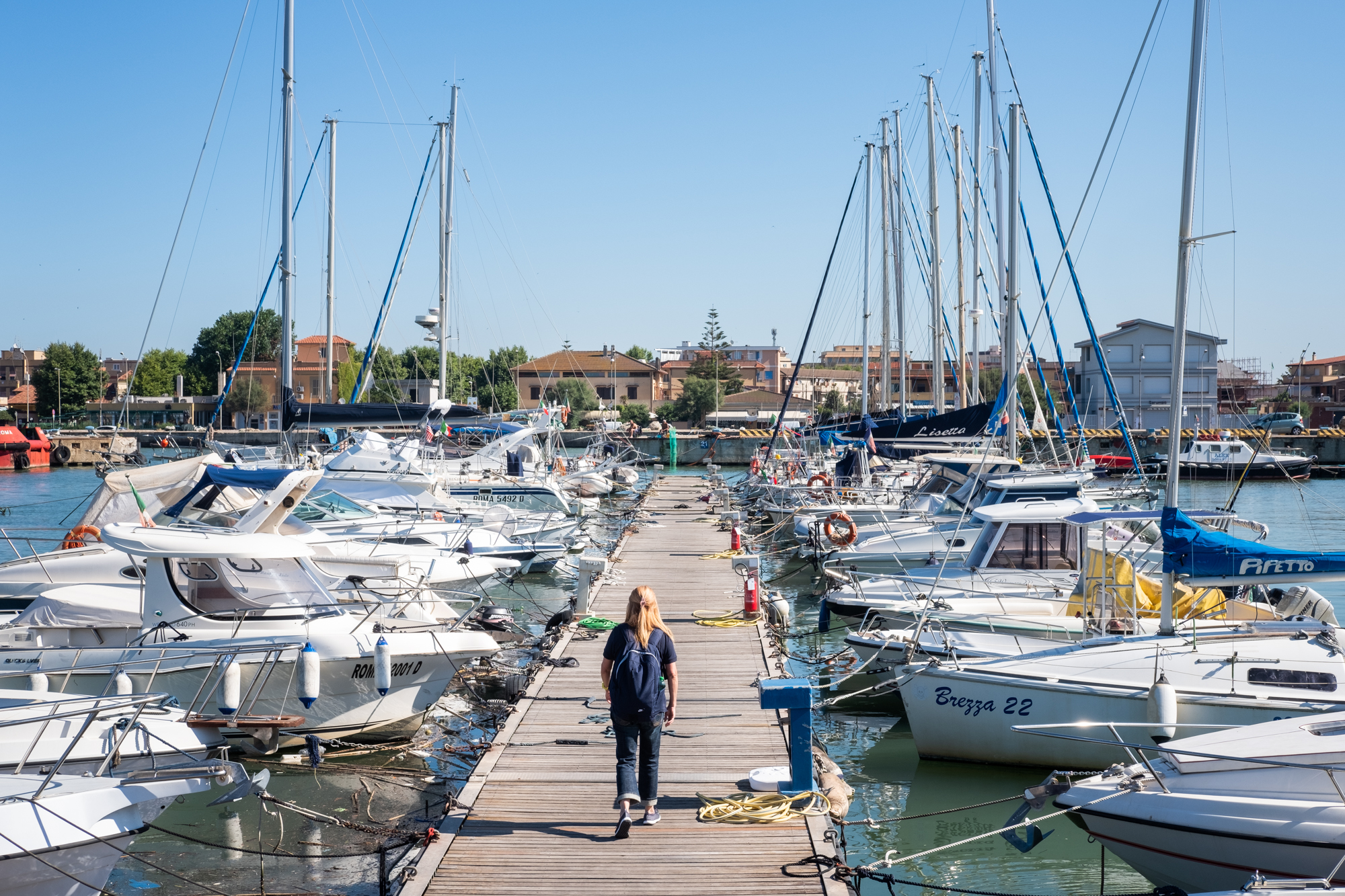 Patrizia Pilloni walks along a Fiumicino Harbor pier in Italy to meet her instructor for a daily sailing lesson.
