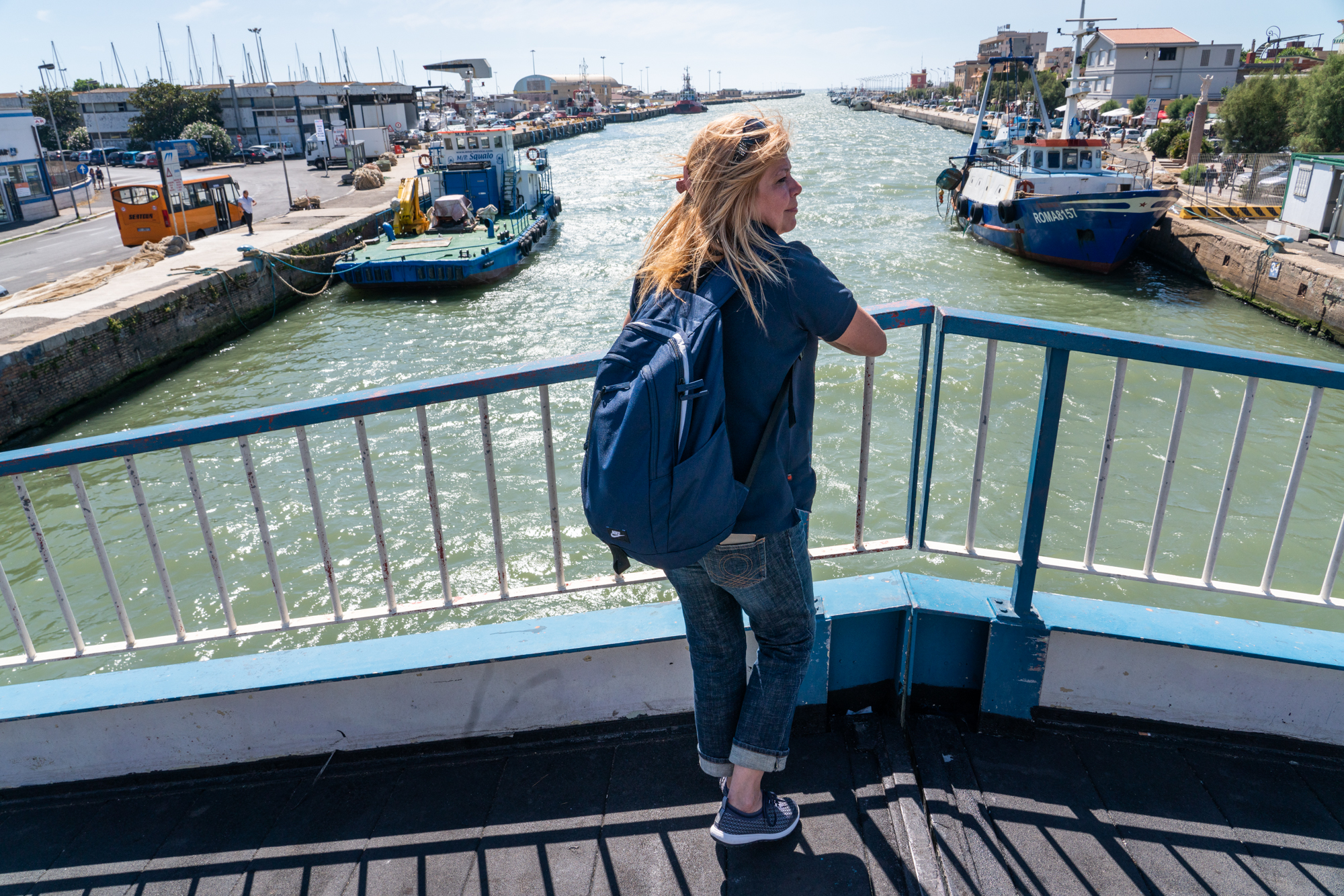 Patrizia pauses on a bridge at the Fiumicino Harbor in Italy. She visits the harbor, where the sailing boat is docked, several times each week for hands-on instruction.