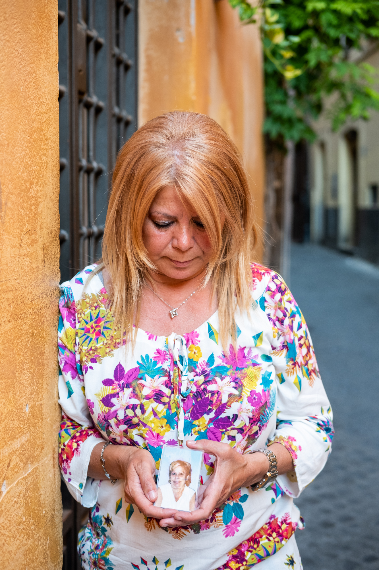 Patrizia Pilloni poses for a portrait along a small street near Campo de'Fiori in Rome, Italy. Patrizia holds a picture of her mother, who was a huge influence on Patrizia to follow her dreams.