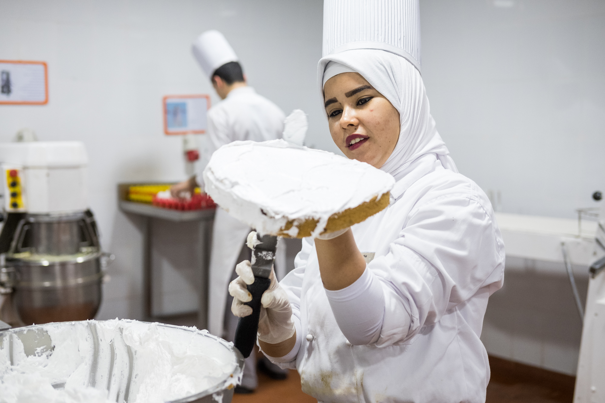 Amira, a trainee in the Kitchen/Pastry Section, prepares a fresh cake and frosting.