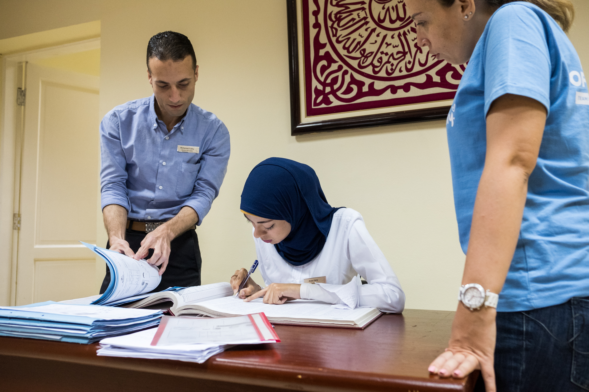 Arwa (center), a trainee in the Human Resources Department at Hilton Sharm Waterfalls Resort in Sharm El Sheikh, Egypt, prepares employee paperwork with the help of her boss (left). Ingy Helal (right), the Hilton Team Member who introduced the program, looks on.