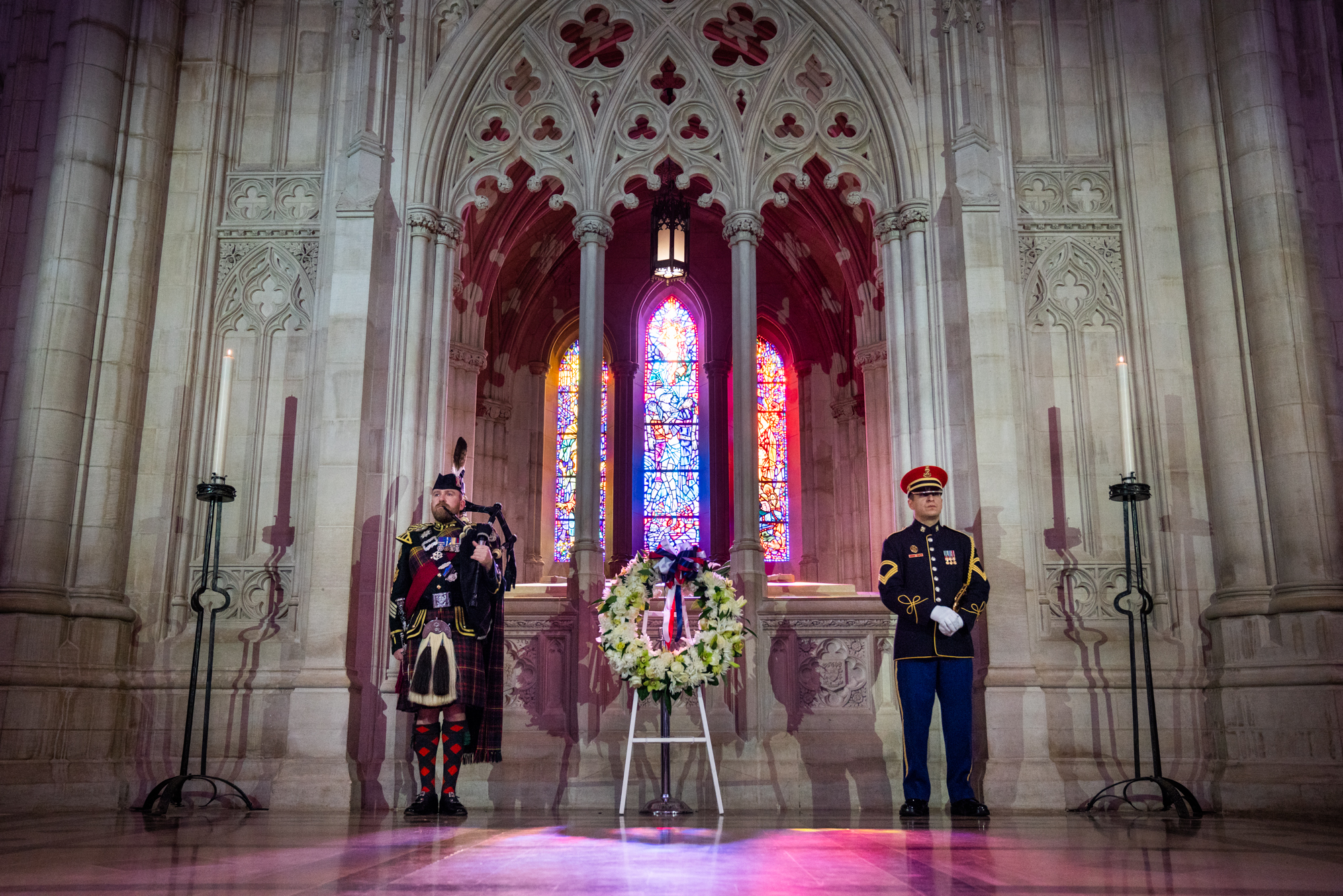Peter MacGregor (left), Warrant Officer Class 2 Pipe Major, and a member of the U.S. Army Band (right) stand at attention alongside the centennial wreath.