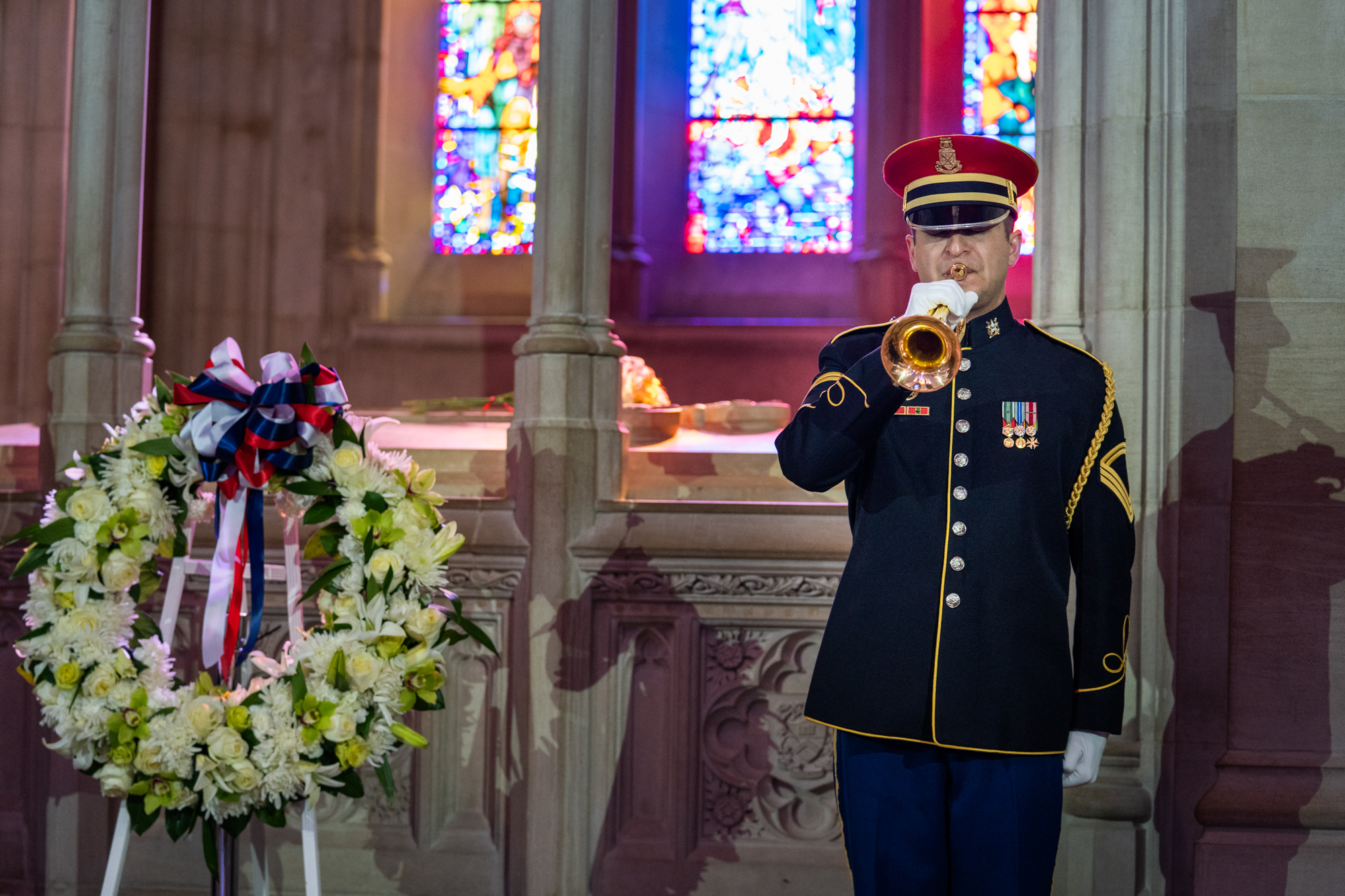 A member of the U.S. Army Band plays Taps while standing alongside the centennial wreath.