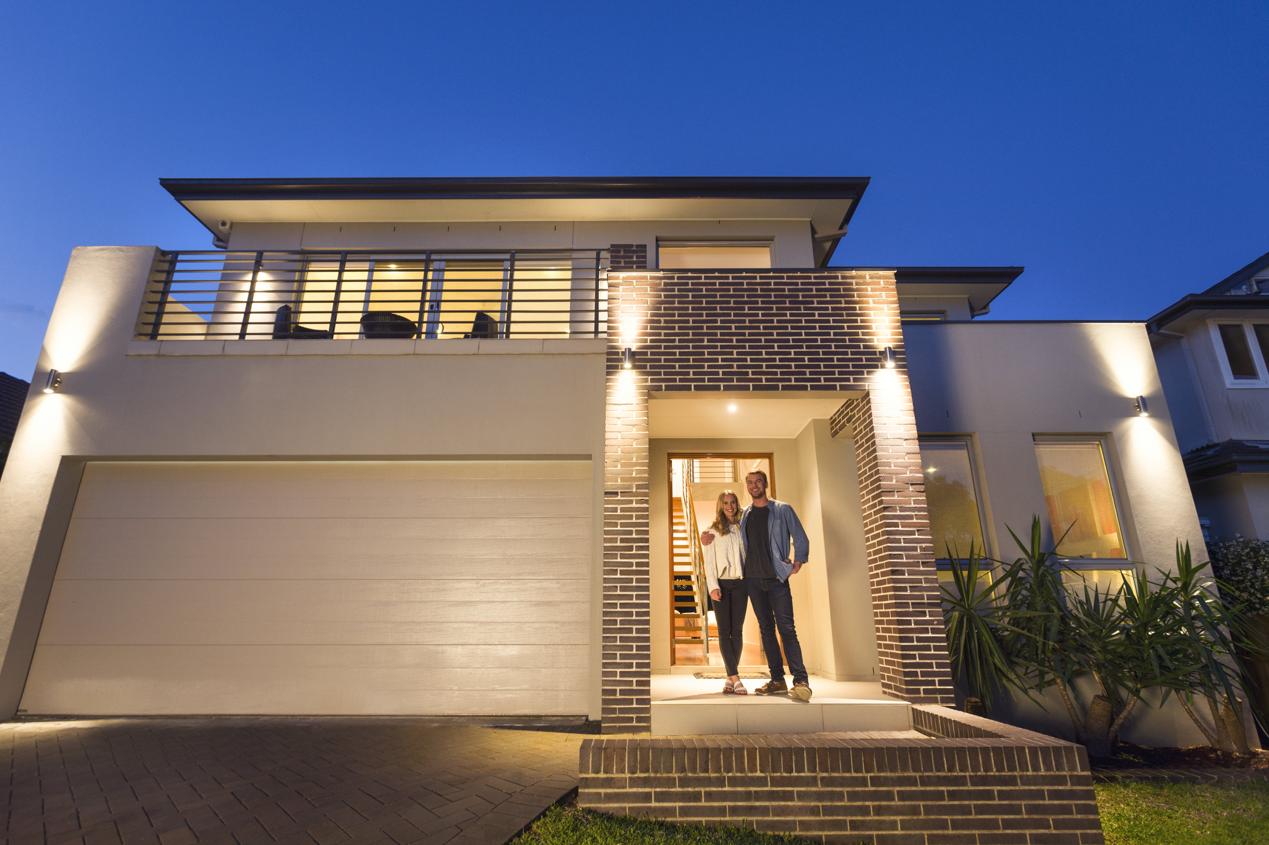 Couple-standing-in-front-of-their-new-home-000085622793_Double.jpg