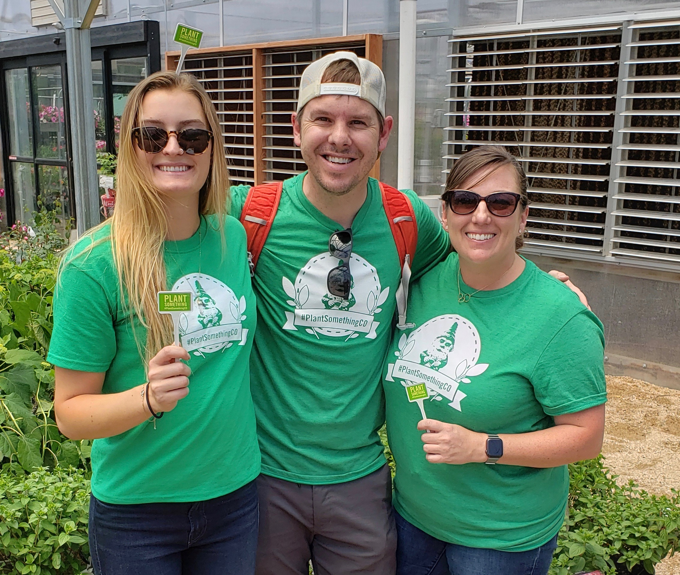Katie, Ben, and Allison hold up their official #PlantSomethingCO stakes after the live event