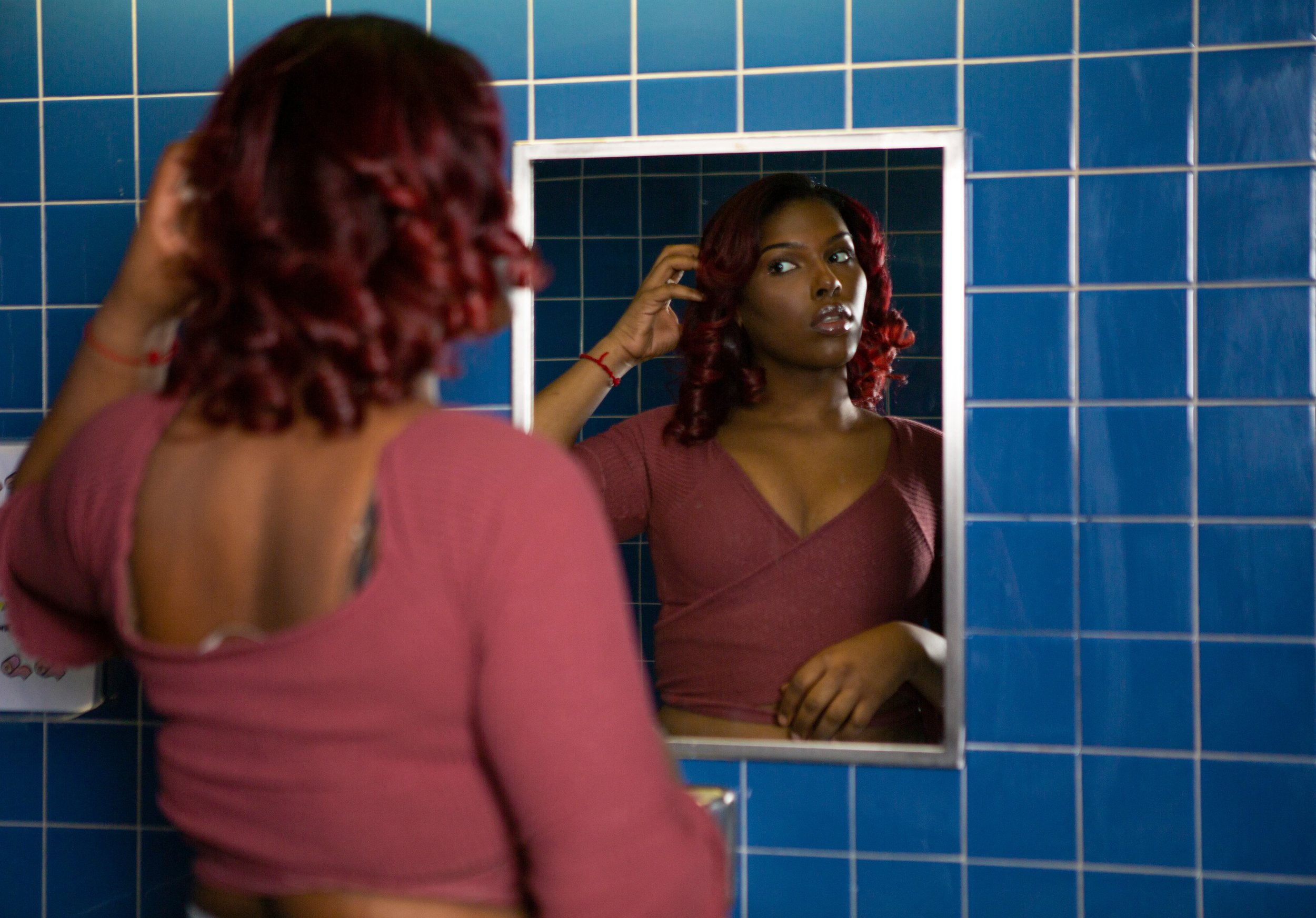 A young transgender woman looking in a bathroom mirror (1).jpg