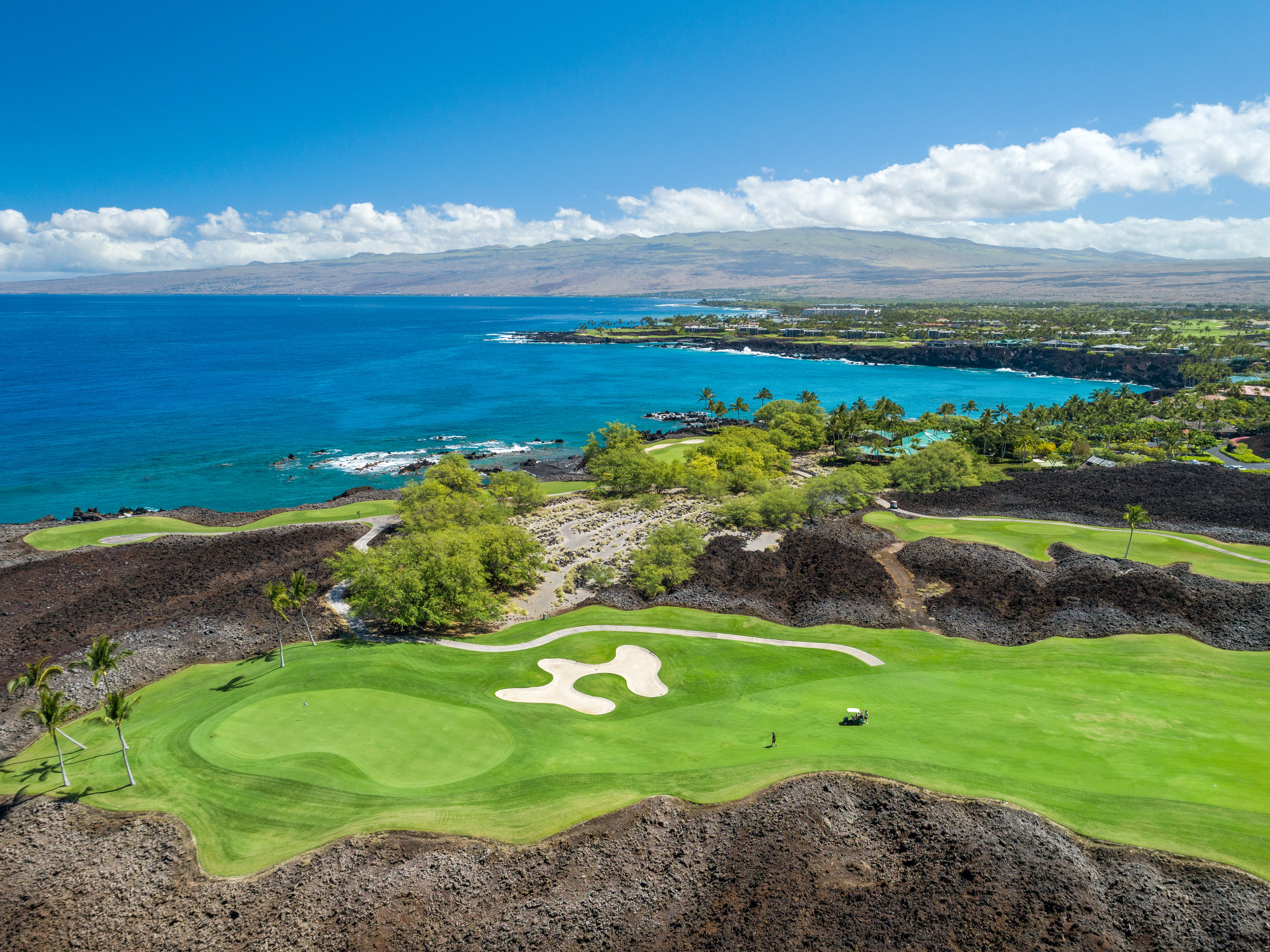 Green fairways against a dramatic black lava backdrop, with ocean and mountain views, as seen from the rear lots at Ke Kailani.