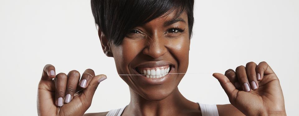 Beautiful woman flosses her healthy teeth