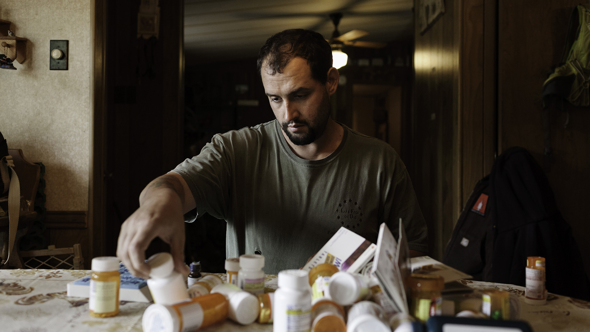 U.S. Army veteran Alex Sutton sorts through an assortment of prescription medications on the kitchen table of his home. After being medically retired from the Army for Chronic PTSD, Sgt. Sutton was given a disability rating of 100% from the Veteran's Administration.