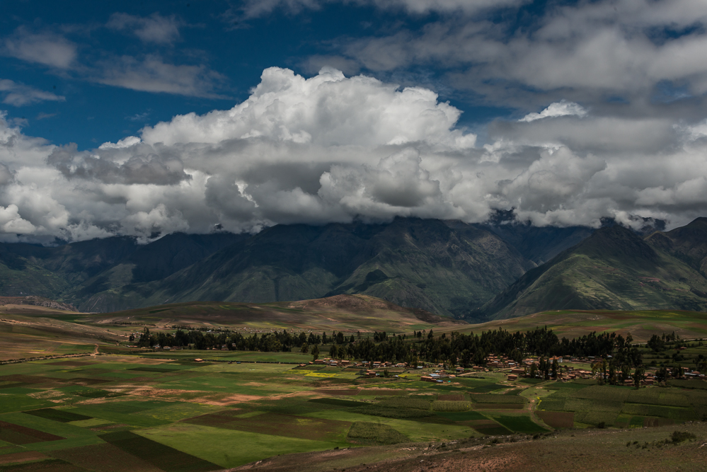 A view of the valley with farms and the mountains at the horizon. The clouds were very nice to appear for the photograph!