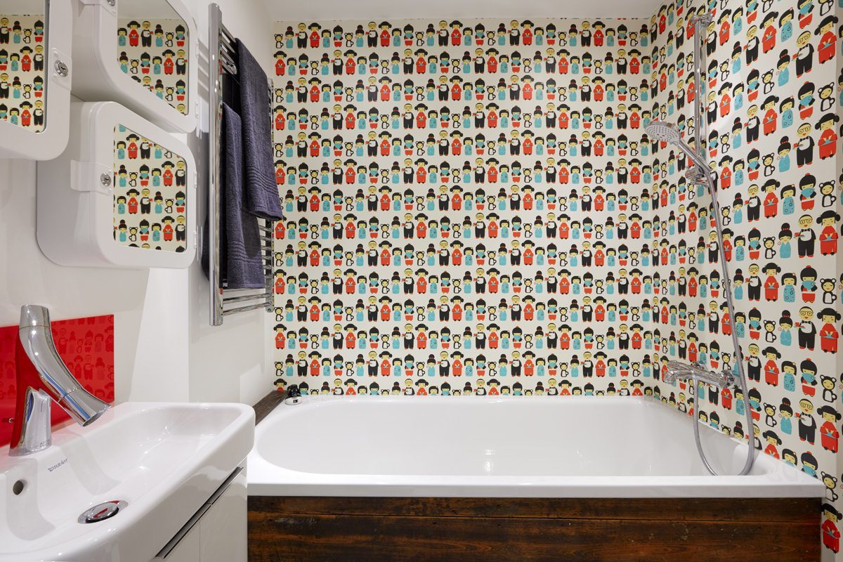 Varnished wallpaper makes a fun alternative to the traditional tile.