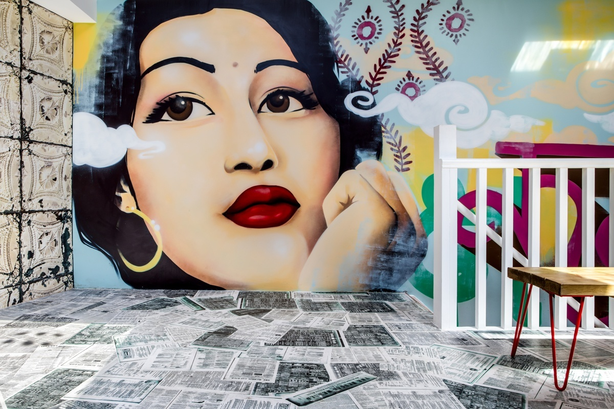 Varnished vintage Indian newspapers create a unique floor in the upstairs dining room while the stunning mural of Indian cinema legend Madhubala designed and created by  Paintshop Studio Ltd keeps a watchful eye.