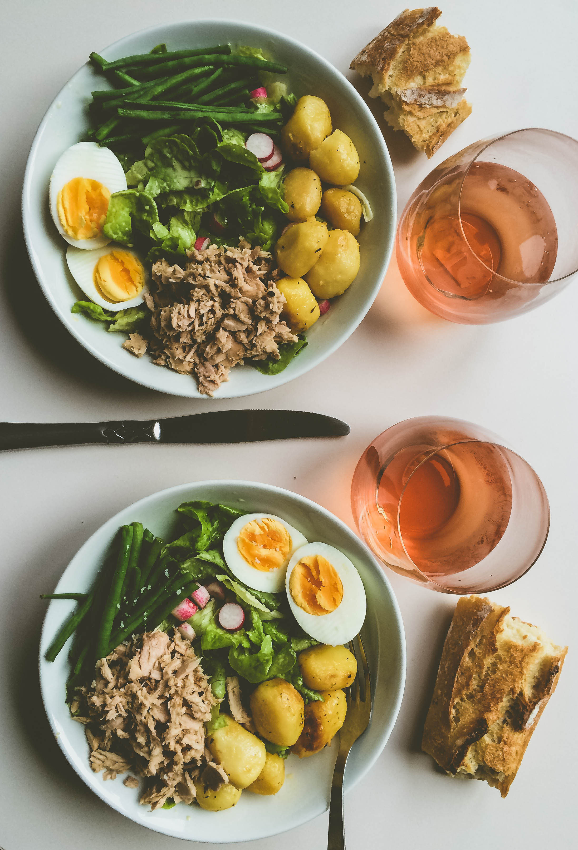 A bright salad made of tuna, potatoes, egg, radishes, green beans with salt and homemade dressing. Baguette and rosé on the side.