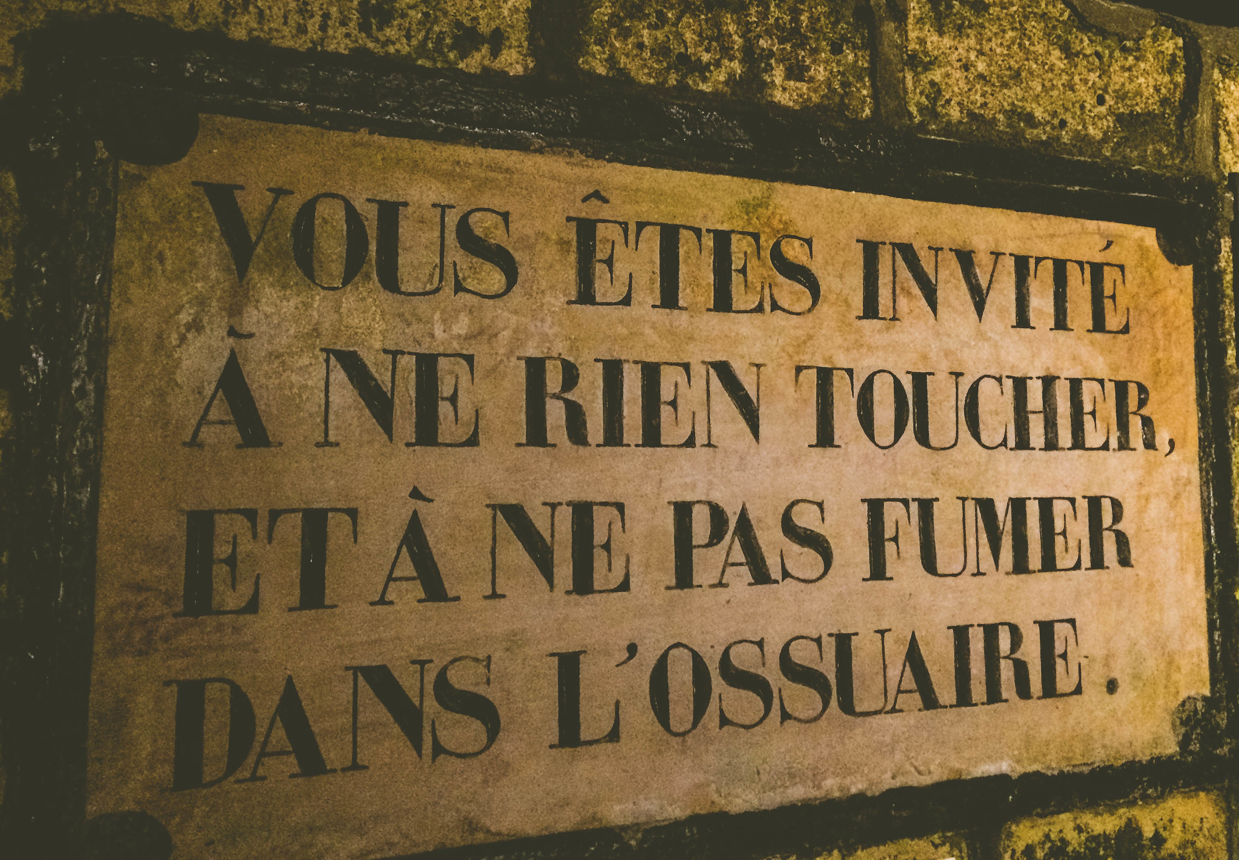 """Roughly translated as """"You are not invited to touch or smoke in the ossuary."""""""