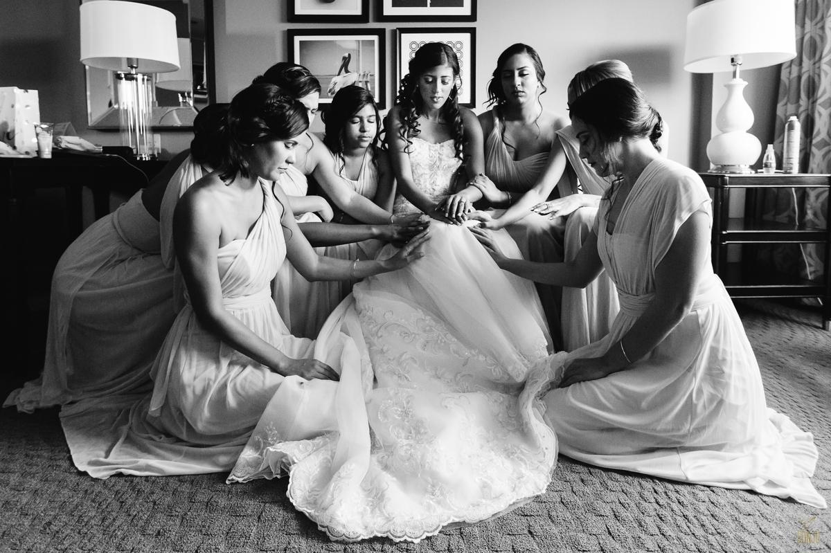 Bride prays with bridesmaids