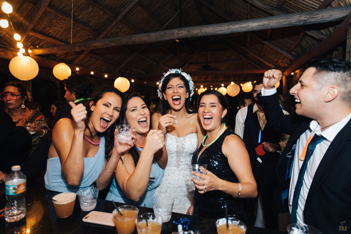 Bride taking shots at bar with bridesmaids