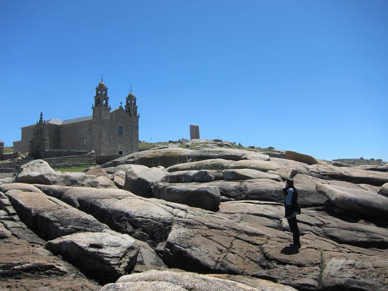 Pedra d'Abalar (rocker stone) in front of Nosa Señora da Barca church in Muxía, Spain.