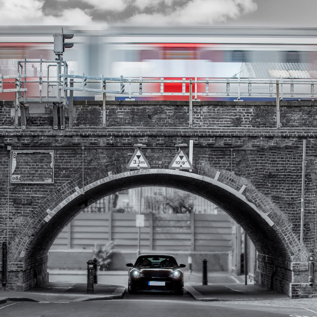 Porsche 996 driving under the arches of London Underground whilst a train passes overhead