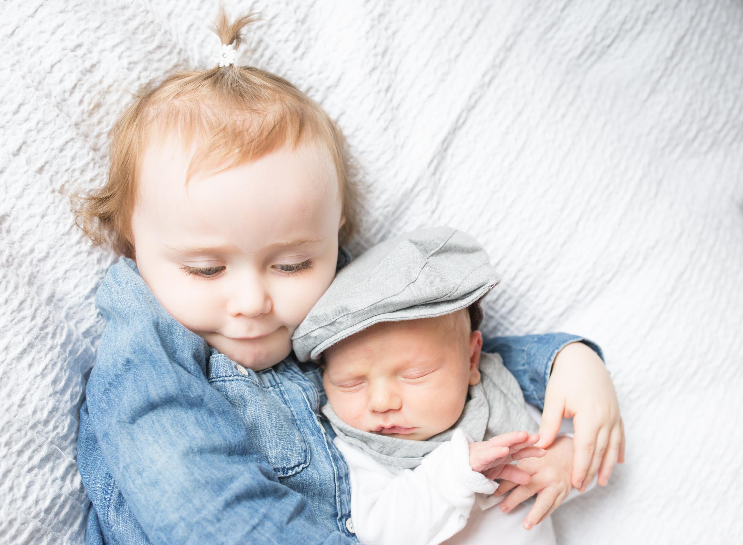 Toddler hugging newborn in Boston Massachusetts