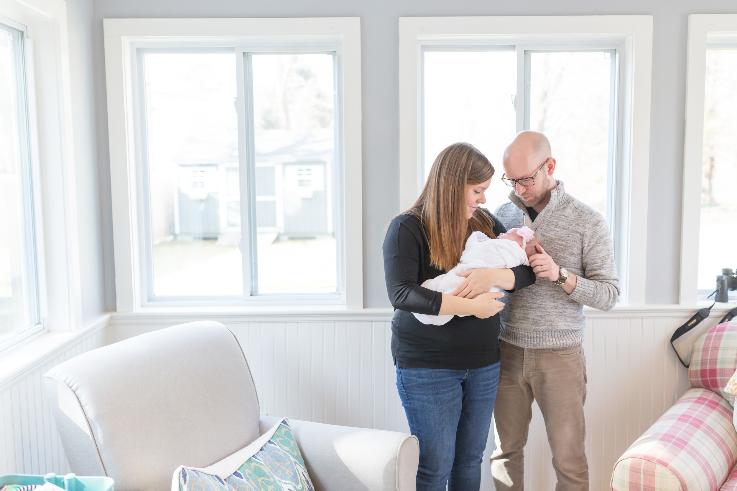 Mom and Dad look at Newborn in Cotuit Massachusetts during in-home session