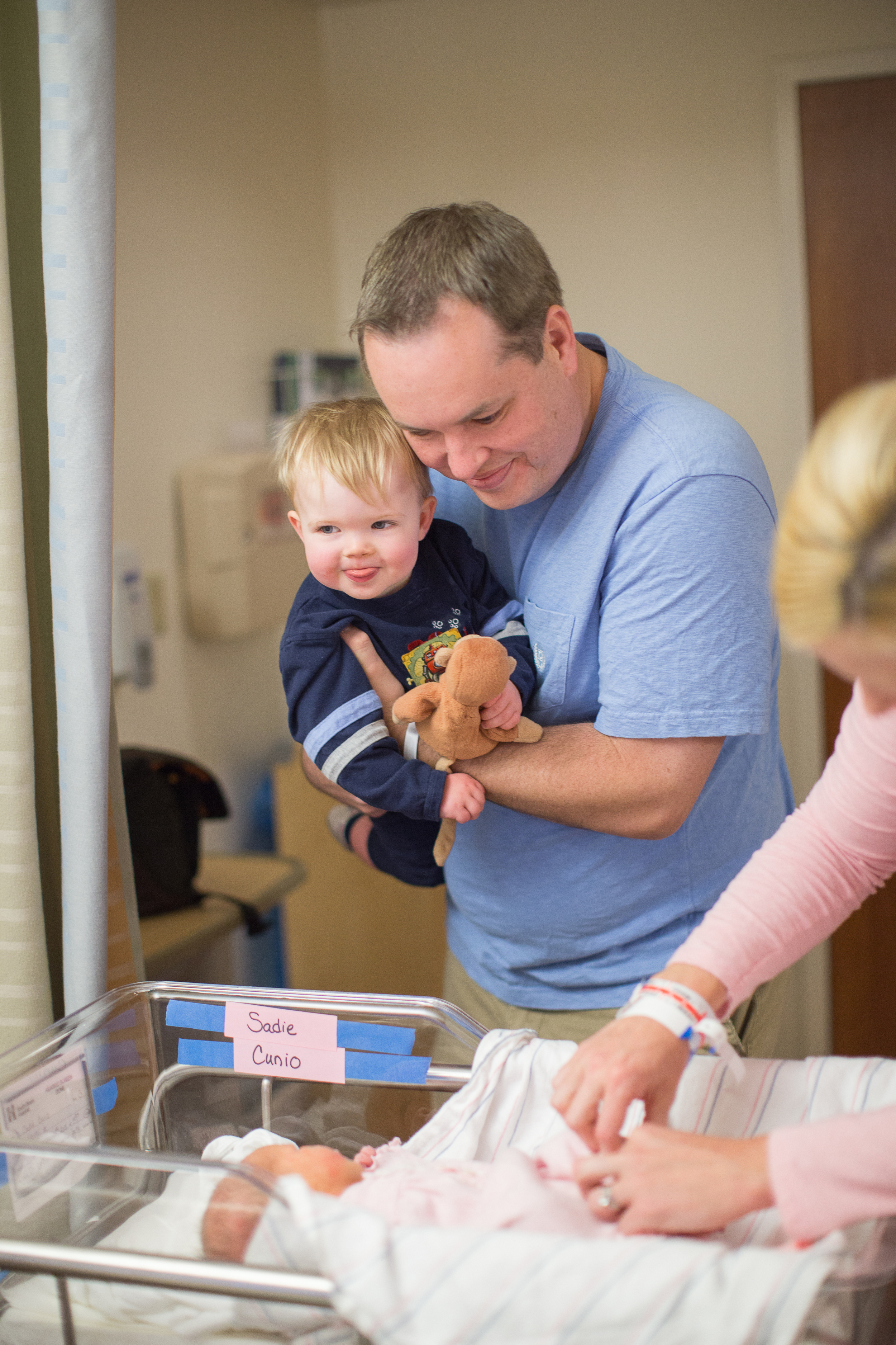 Dad looks at Newborn with toddler in his arms Boston Massachusetts