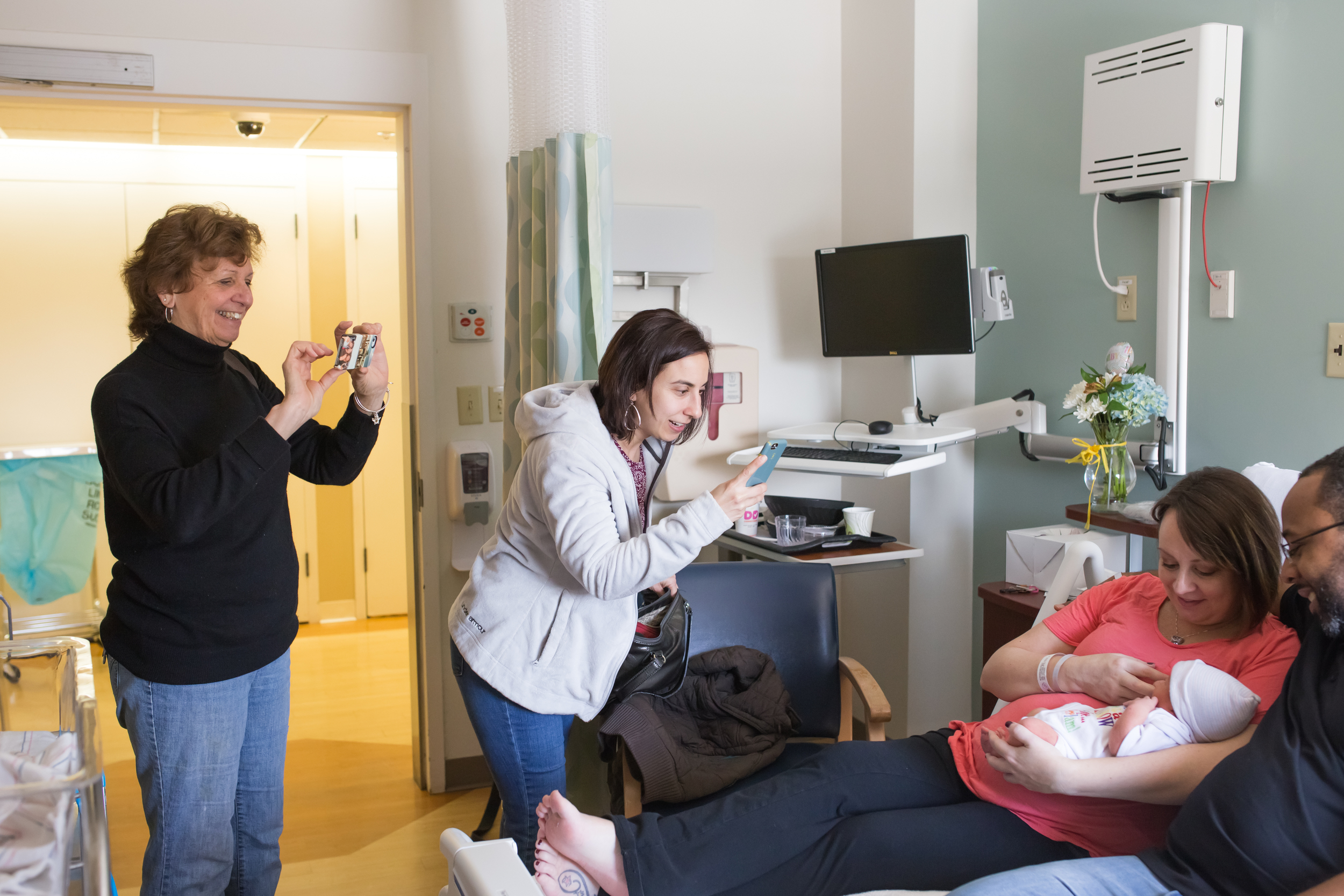 Mom and family taking photos of new baby in Boston Massachusetts during Fresh 48 session