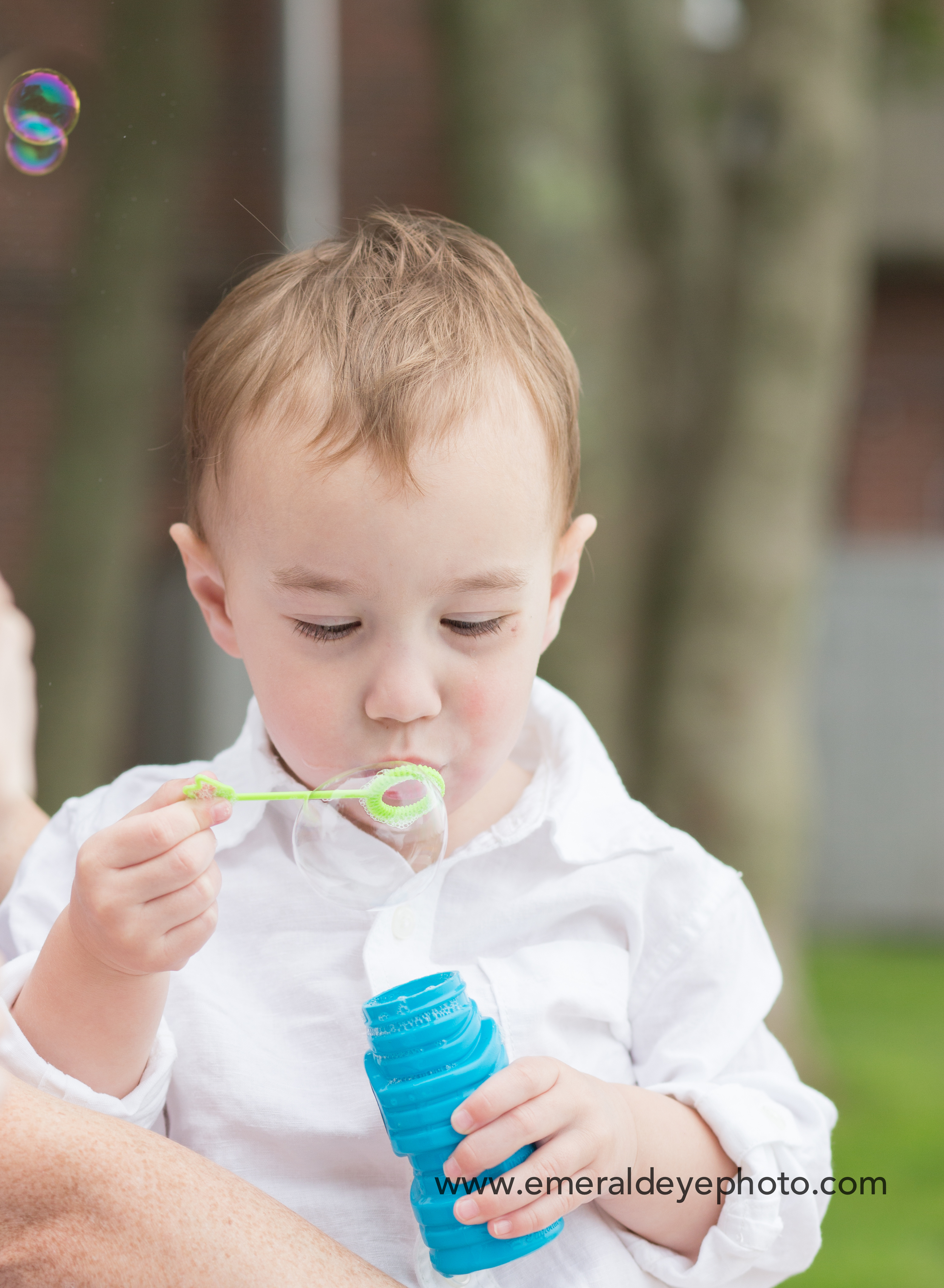 Toddler blows bubbles during family session on Cape Cod Massachusetts