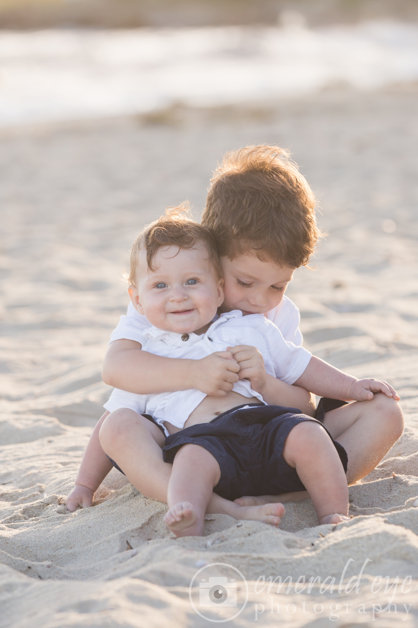 Big brother holds little brother in the sand with big smiles during a Family session on Cape Cod Massachusetts