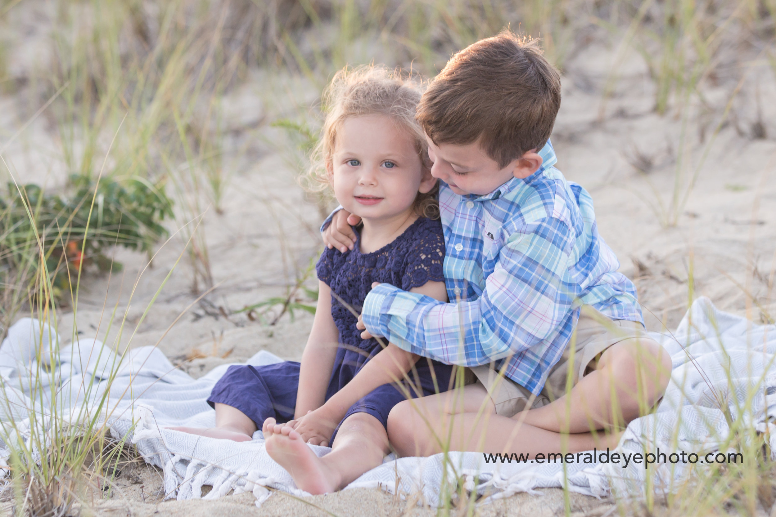 Brother and sister sit in the sand at South Cape beach in Mashpee Massachusetts
