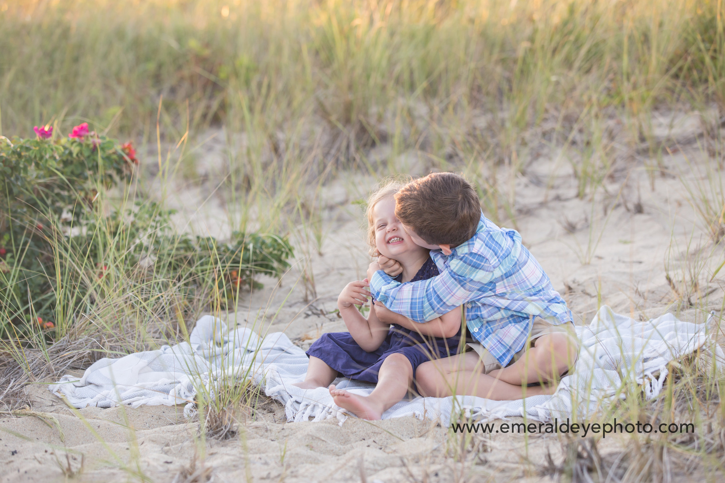 Brother kisses sister in the dunes at South Cape Beach in Massachusetts