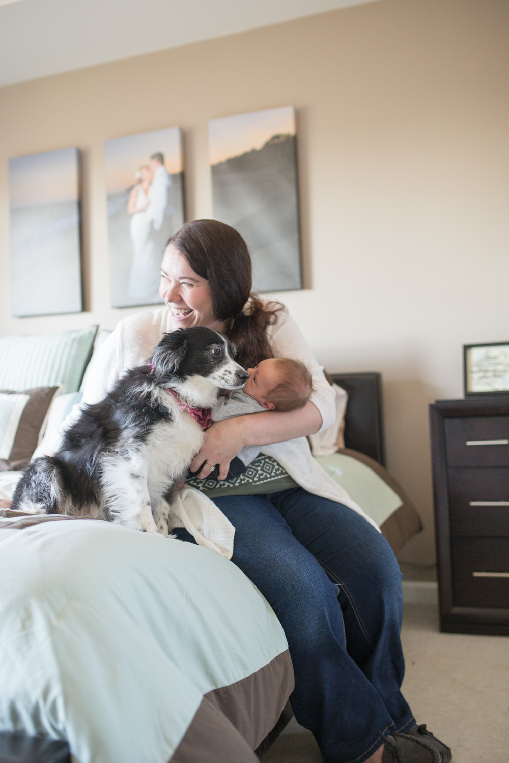 Mom holding Newborn in-home session in Boston with dog watching