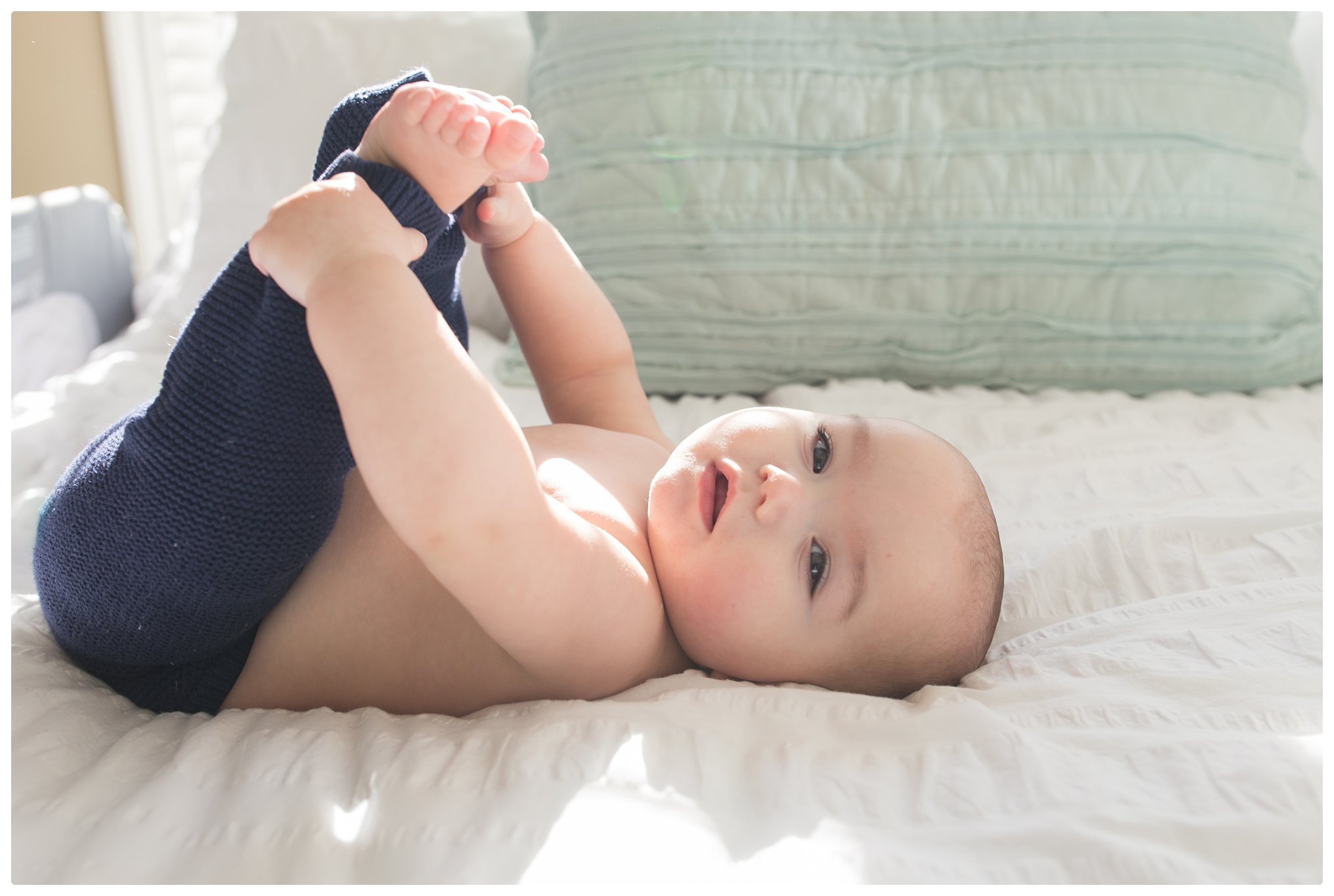 Six month old laying on bed holding his feet during relaxed Lifestyle session in Massachusetts