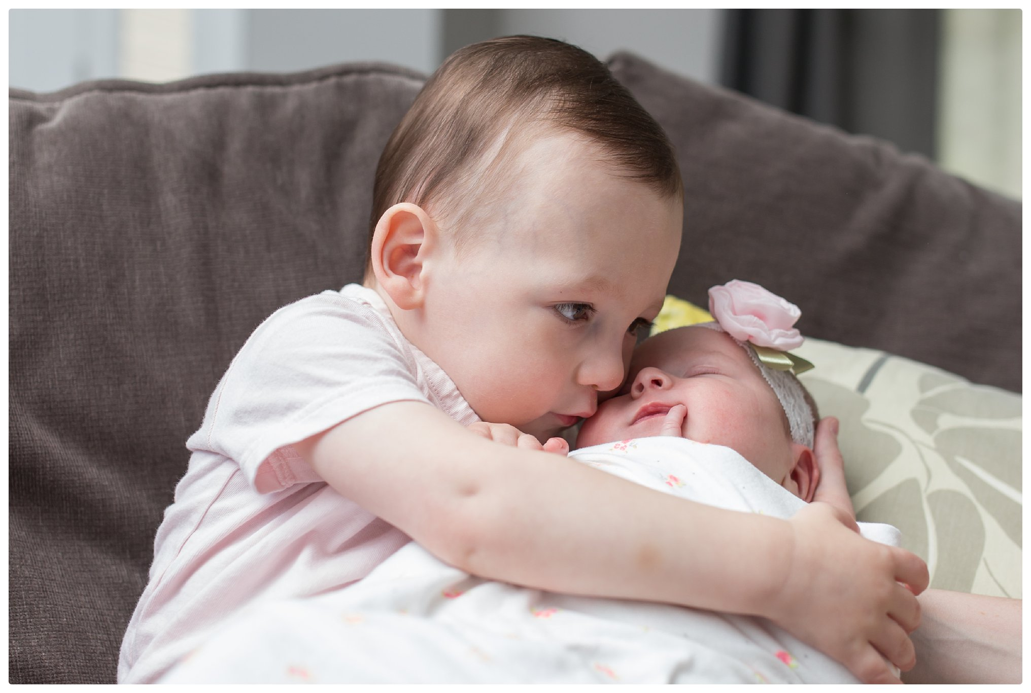 Big brother snuggles little baby sister during a Newborn Lifestyle photo captured by a Boston Newborn Photographer in Massachusetts.