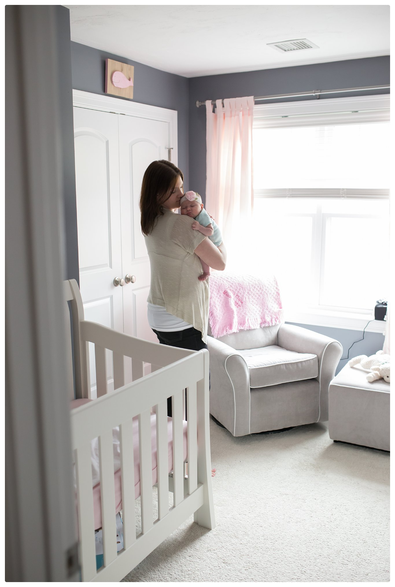 Mom and baby in nursery during Newborn Lifestyle photos in Boston Massachusetts.