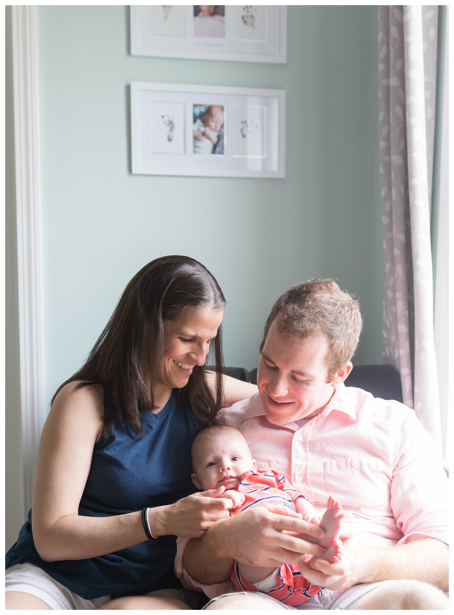 Mom and Dad hold newborn during in-home relaxed newborn photo session in Massachusetts