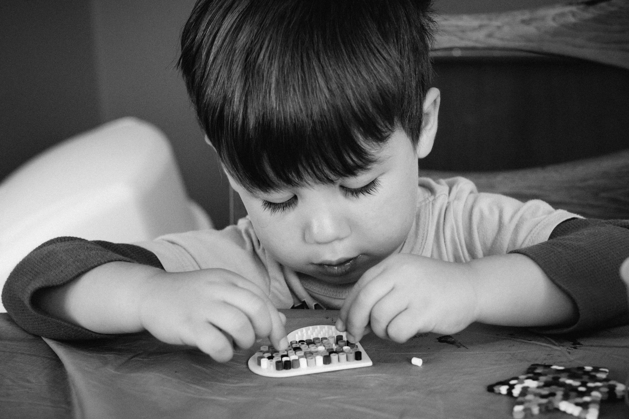 Focusing on his perler beads.