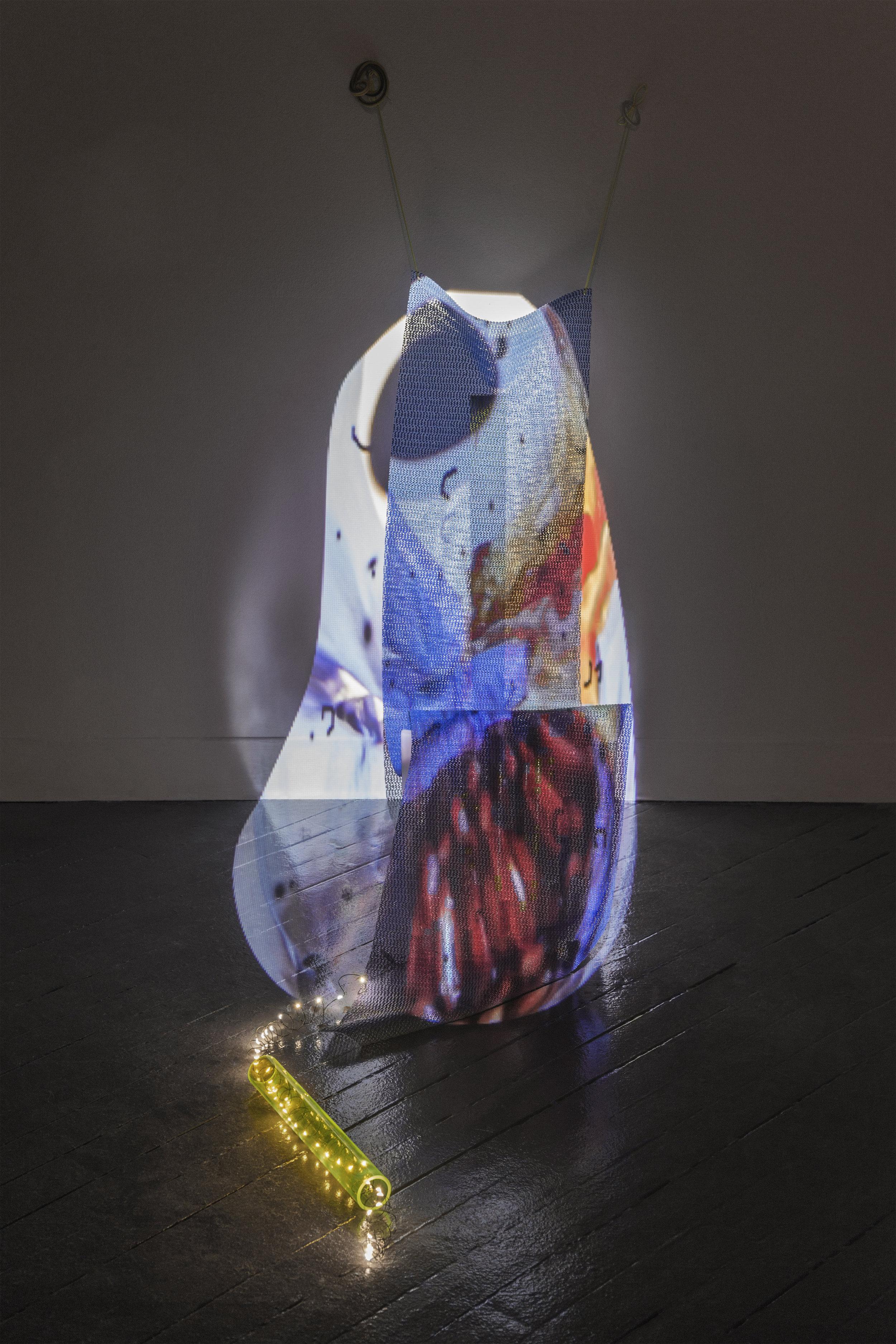 Untitled (Pomegranate-Kite), 2015, still of video sculpture including shelf lining, plastic, tiles, LED light string, dimensions variable